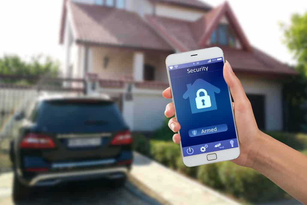 Secure your home using a Hand holding mobile phone displaying a security app outside a home with a car in the drive