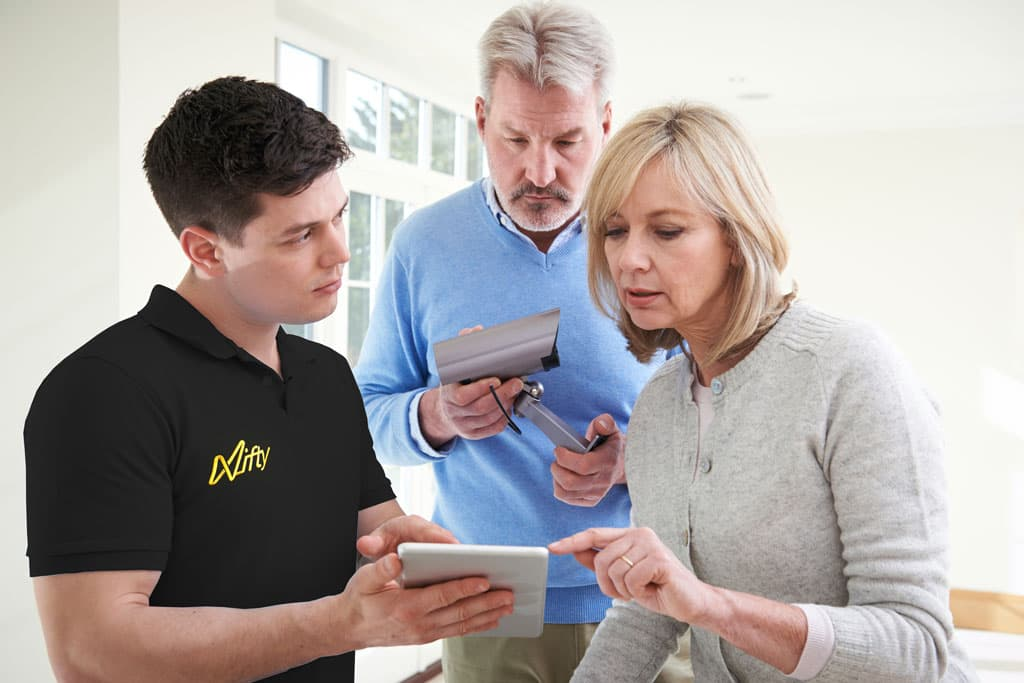 Older couple consulting with a Nifty engineer in a black top about their home and pointing to a tablet